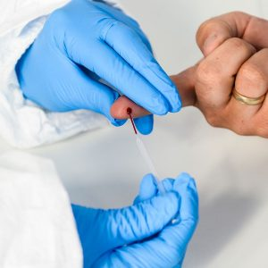 A small blood sample is taken by a health care professional.
